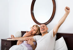 Mature loving couple lounging in bed after awaking cuddling stock images