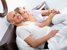 Mature loving couple lounging in bed after awaking cuddling Royalty Free Stock Photography