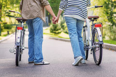 Mature loving couple walking with bikes Royalty Free Stock Photography