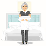 Mature maid woman with towels and bed sheets. House cleaning service concept Royalty Free Stock Images