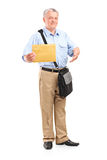 Mature mailman holding an envelope Royalty Free Stock Images