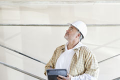 Mature male architect making a note in digital tablet while looking up at construction site Royalty Free Stock Photo