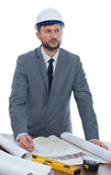 Mature male architect thinking while working on a blueprint stock photo