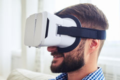 Mature male with beard working in VR glasses sitting on sofa. Close-up of mature male with beard working in VR glasses sitting on sofa Stock Images