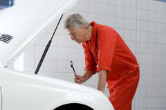 Mature male car mechanic, in red overalls, looking at car engine in auto repair shop, holding wrench, side view Royalty Free Stock Photos
