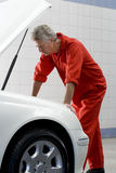 Mature male car mechanic, in red overalls, looking at car engine in auto repair shop, side view Royalty Free Stock Photos