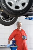 Mature male car mechanic, in red overalls and protective gloves, taking tea break near hydraulic platform in auto repair shop, smi Royalty Free Stock Image