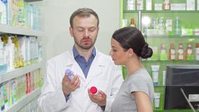 Mature male chemist helping his female customer choosing between two items. Young woman talking to pharmacist, shopping for cosmetics at local drugstore stock video