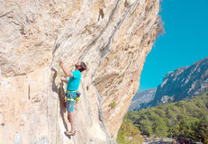 Mature male Climber making Move on vertical Rock Royalty Free Stock Images