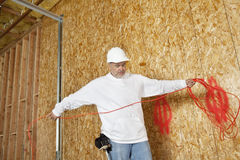 Mature male construction worker with an electrical wire Royalty Free Stock Images