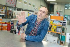 Mature male customer seeking advise from seller at hardware store. Man royalty free stock photos