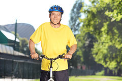 Mature male cyclist posing in a park with bike Royalty Free Stock Image