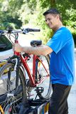 Mature Male Cyclist Taking Mountain Bike From Rack On Car. Mature Male Cyclist Takes Mountain Bike From Rack On Car Stock Image