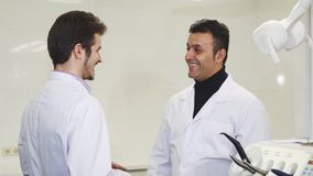 Mature male dentist shaking hands with his colleague royalty free stock photography