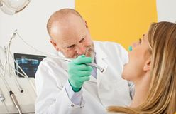 Dentist using dental drill on female patient. Mature male dentist using dental drill on female patient - dental decay treatment Stock Images