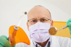 Dentist holding instruments, looking down Royalty Free Stock Image