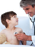 Mature male doctor checking little boy's pulse Stock Photography
