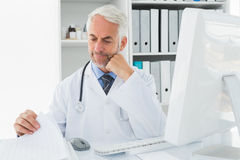 Mature male doctor with computer at medical office. Handsome mature male doctor sitting with computer at medical office stock photography