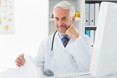 Mature male doctor with computer at medical office Stock Photos