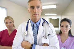 Mature male doctor flanked by two female nurses, standing in hospital corridor, portrait Stock Photography