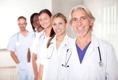 Mature male doctor with his team of colleagues. Out of focus behind him Stock Photography