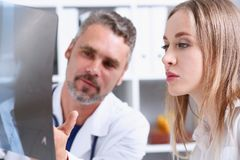 Mature male doctor hold in arm and look at xray photography Royalty Free Stock Image