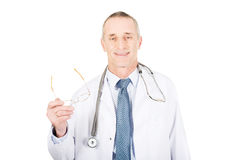 Mature male doctor holding his eyewear Royalty Free Stock Images