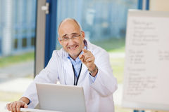 Mature Male Doctor Pointing In Clinic Stock Image