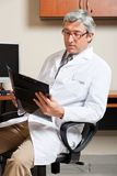 Mature Male Doctor Reading Royalty Free Stock Images