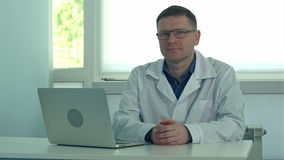 Mature male doctor sitting at desk with laptop and looking at camera in his clinic office stock video