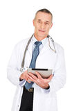 Mature male doctor using a tablet Stock Photo