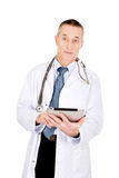 Mature male doctor using a tablet Royalty Free Stock Photos