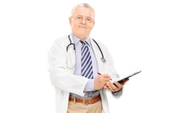 Mature male doctor writing on clipboard. Isolated against white background Stock Image