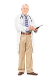 Mature male doctor writing on clipboard Royalty Free Stock Photo