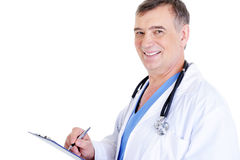 Mature male doctor writing something. Successful laughing mature male doctor writing something Royalty Free Stock Photography