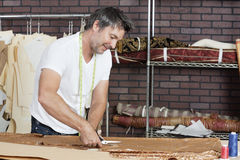 Mature male dressmaker cutting fabric in design studio royalty free stock images
