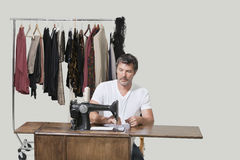 Mature male dressmaker sitting at sewing machine over colored background Stock Photography