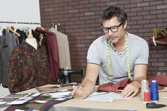 Mature male fashion designer working in design studio Stock Photography
