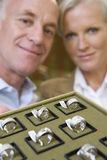 Mature male and female jewellery shop assistants with tray of rings, smiling, portrait Stock Photos
