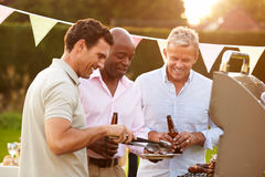 Mature Male Friends Enjoying Outdoor Summer Barbeque Stock Photography