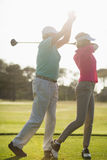 Mature male golf player teaching woman. Mature male golf player teaching women while standing on field Royalty Free Stock Images