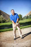 Mature Male Golfer. A vertical photo of a mature male golfer about to hit out of a sand bunker around the green of a golf course Stock Images