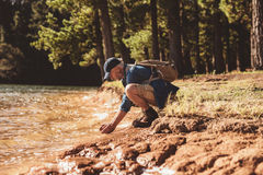 Mature male hiker washing face in lake Stock Photo