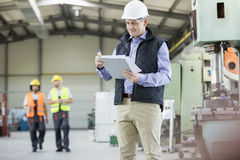 Mature male inspector writing on clipboard while workers in background at factory stock image
