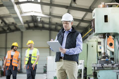 Mature male inspector writing on clipboard while workers in background at industry royalty free stock photos