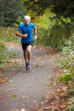 Mature Male Jogger Running Along Path Royalty Free Stock Photo