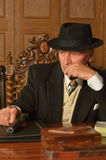 Mature male mafia boss. On the table with gun Royalty Free Stock Images
