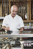 Mature male merchant at gun shop with credit card reader stock images