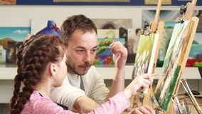 Mature male painter artist helping his cute daughter with a painting royalty free stock images