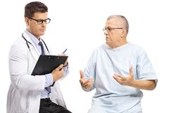 Mature male patient talking to a doctor writing royalty free stock image